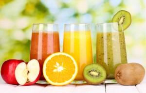 fresh fruit juices on wooden table, on green background