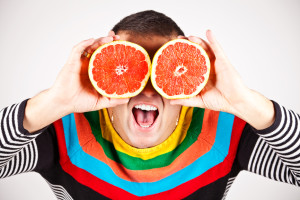 Young man holding slices of grapefruits to his eyes on white background.